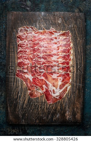 Slices of coppa meat on rustic wooden background. Traditional Italian specialty made from pork neck . Top view - stock photo