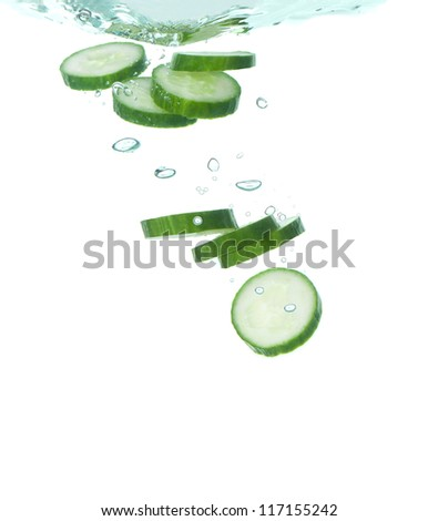 Slices of cucumber falling into clear water - stock photo