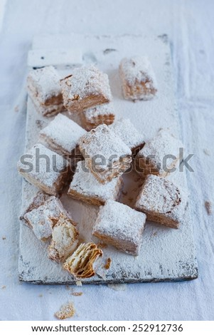 Slices of delicious homemade puff pastry sifted with  powder, arranged on vintage wooden table. Homemade cookies on puff pastry. Taken on a white background.  White country style kitchen. Rustic style - stock photo