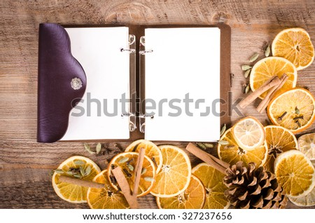 Slices of dried orange, lemon, cinnamon, cloves, cardamom and notebook. Free space for text. - stock photo
