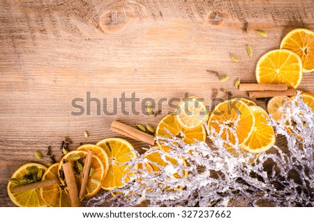 Slices of dried orange, lemon, cinnamon, cloves, cardamom and wreath on wooden background - stock photo
