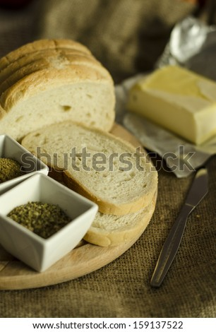 slices of fresh bread with butter, spices and herbs on wooden board