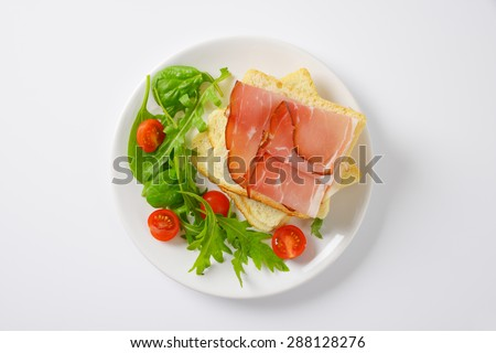 slices of fresh bread with dried pork ham, rucola and spinach leaves and halved cherry tomatoes on white plate - stock photo