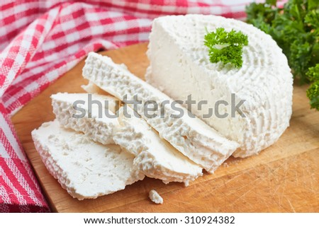 slices of fresh cottage cheese on wooden cutting board  - stock photo