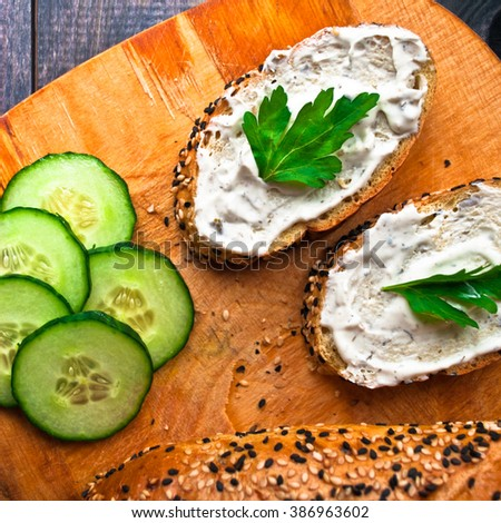Slices of fresh cucumber, baguette with sesame and sandwich with cream cheese and parsley on wooden cutting board. Close up - stock photo