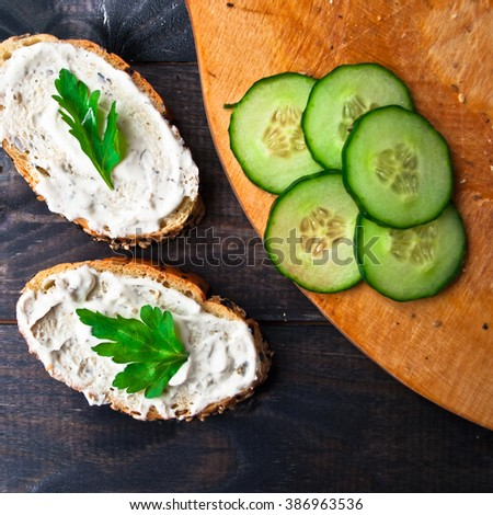Slices of fresh cucumber on beige cutting board and sandwich with cream cheese and parsley on rustic wooden background. Top view - stock photo