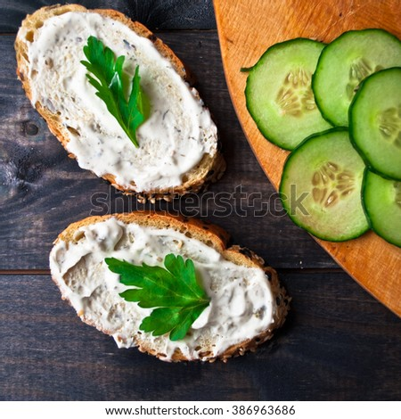 Slices of fresh cucumber on cutting board and sandwich with cream cheese and parsley on rustic wooden background - stock photo