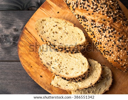 Slices of fresh homemade baguette served on beige cutting board. Top view - stock photo