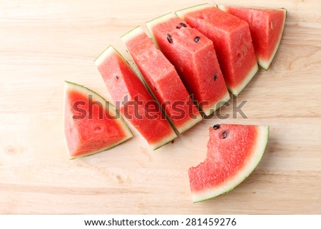 Slices of fresh watermelon on wooden background - stock photo