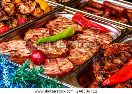 Slices of fried ham, ready to be served at a street fair. Christmas Decorations. - stock photo