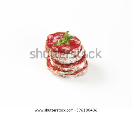 Slices of fuet sausage on white background - stock photo