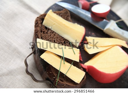 Slices of Gouda cheese with dark bread and chives on cutting board with room for text - stock photo