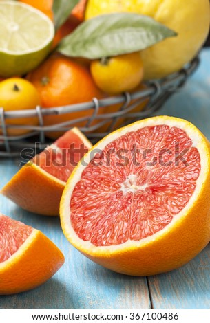 slices of grapefruit, different fresh citrus fruit in a basket on a blue wooden background
