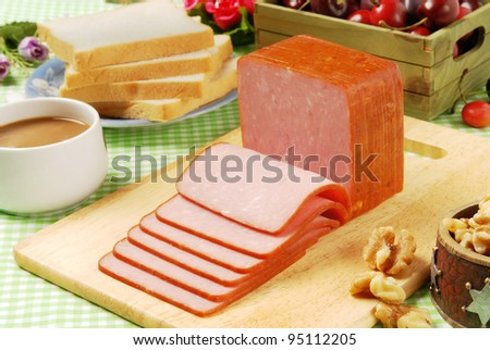 Slices of ham on a wooden board. - stock photo