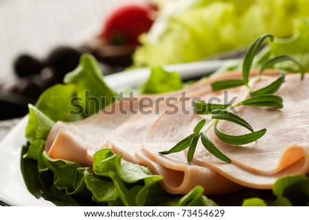 Slices of ham on lettuce with rosemary. - stock photo