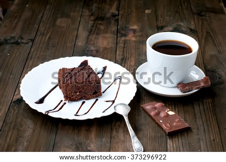 slices of homemade chocolate brownies with nuts on a plate and a cup of coffee - stock photo