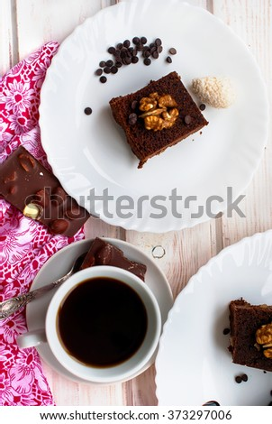 slices of homemade chocolate brownies with nuts on a plate and a cup of coffee