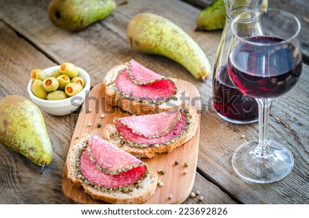 Slices of italian salami with pears and wine - stock photo
