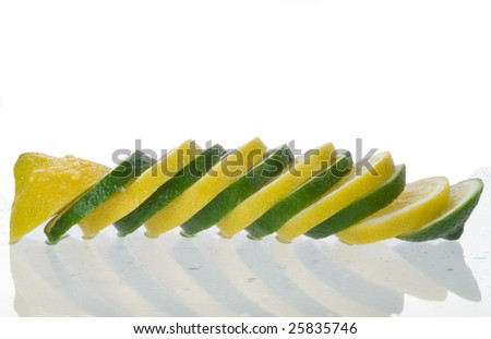 Slices of lemon alternated with slices of lime sitting on glass with water droplets. Isolated on white with clipping path.