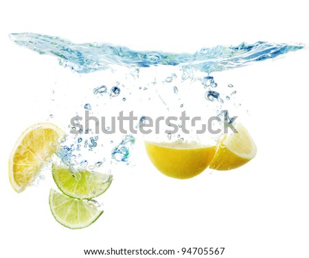 slices of lemon and lime in the water - stock photo