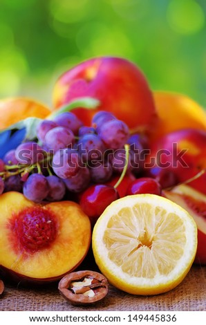 Slices of lemon and peach, fruits in background - stock photo