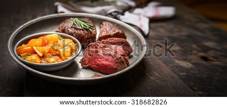 Slices of medium rare roasted meat steak and salsa sauce on rustic wooden background, banner - stock photo