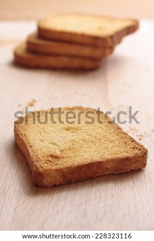 Slices of melba toast on a wooden board - stock photo
