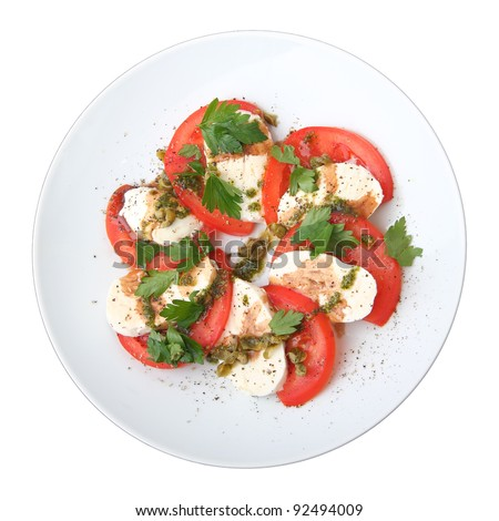 slices of mozzarella and  tomato with fresh basil and capers sauce on white dish, top view. - stock photo