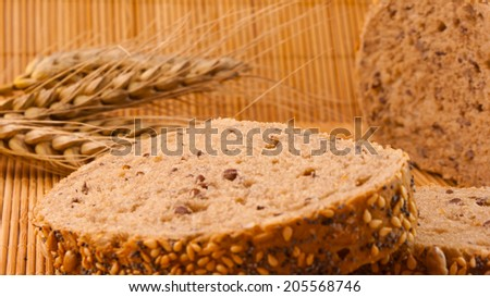 Slices of organic bread decorated with natural cereals on wooden background and wheat