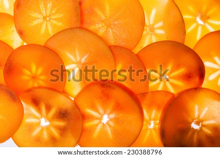 Slices of persimon fruit, illuminated from behind - stock photo