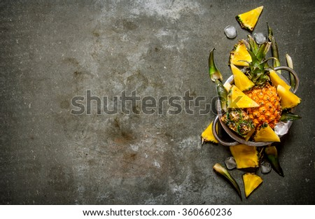 Slices of pineapple from a whole pineapple , leaves and ice in a saucepan. On the stone table. Free space for text . Top view - stock photo