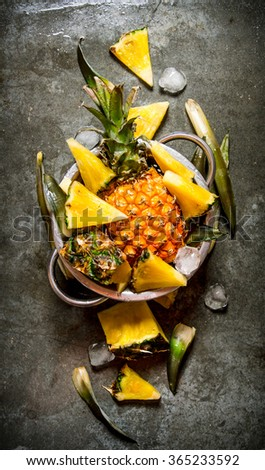 Slices of pineapple from a whole pineapple , leaves and ice in a saucepan. On the stone table. Top view - stock photo