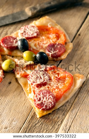 Slices of pizza with salami, tomatoes and olives
