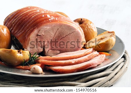 Slices of pork roast on a silver platter with baked apples and roasted veggies, isolated on white - stock photo
