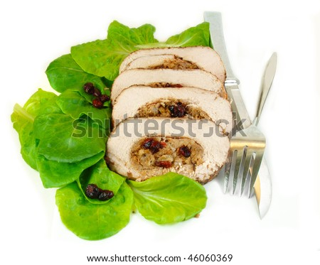 Slices of pork roast stuffed with apple and cranberry stuffing on a bed of lettuce. - stock photo