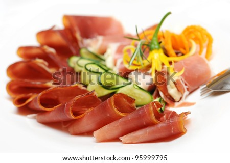 Slices of prosciutto rolled up and arranged with cucumber and papper - stock photo