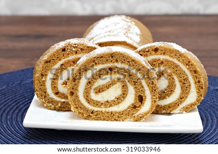 Slices of pumpkin roll cake in front of the whole cake.  Close up with copy space. - stock photo