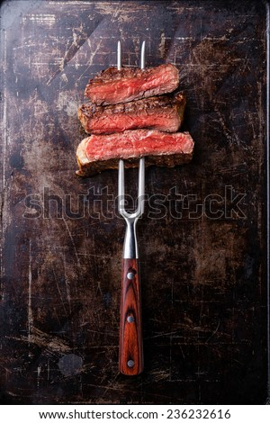 Slices of Rare beef steak on meat fork on dark background - stock photo