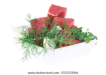 slices of raw fresh beef meat fillet in a white bowls with dill and green peppers isolated over white background - stock photo