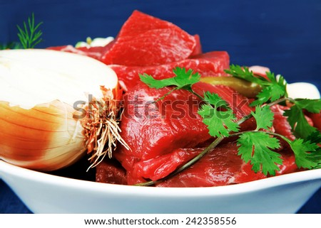 slices of raw fresh beef meat fillet in a white bowls with garlic and red peppers serving on blue table with cutlery - stock photo