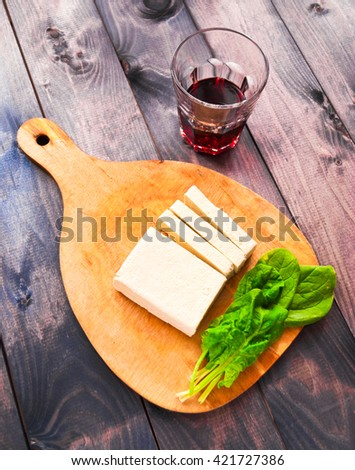 Slices of raw tofu and green leaves of fresh spinach on shabby cutting board and glass of red wine on wooden background - stock photo