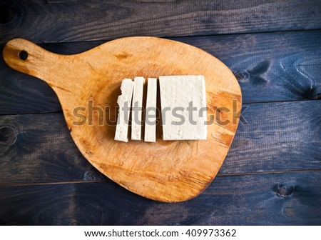 Slices of raw tofu on shabby cutting board - stock photo