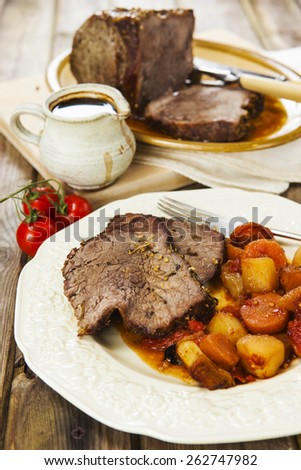 Slices of roast beef and garnish with fork on vintage plate over rustic wooden table with tomatoes, jug of sauce, roast beef joint on oval plate and carving set on the background - stock photo