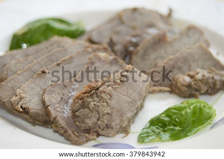 slices of roast beef served whithout seasoning and with only basil and olive oil - stock photo