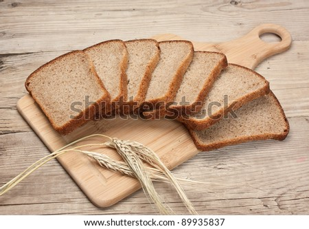 slices of rye bread and ears of corn on the wooden table