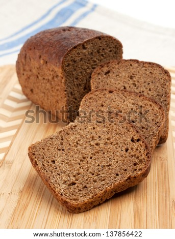 Slices of rye bread on a wooden cutting board. - stock photo