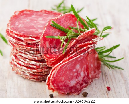 Slices of salami sausage on wooden table. Selective focus - stock photo