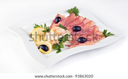 Slices of salted salmon and smoked fat served with lemon and olives