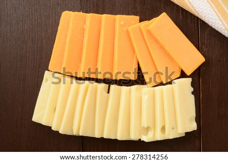 Slices of sharp cheddar and swiss cheeses - stock photo