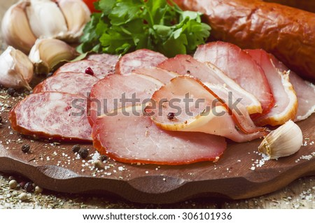 Slices of smoked ham and sausages on a cutting board in a rustic style, selective focus - stock photo
